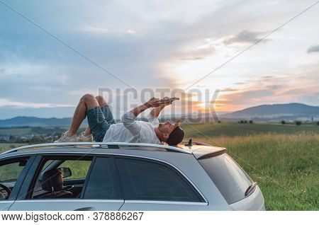 Young Man Lying On The Car Roof And Reading The Paper Bestseller Book.he Stopped His Auto On The Mea