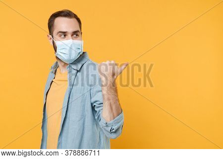 Side View Of Young Man In Sterile Face Mask Posing Isolated On Yellow Wall Background Studio Portrai