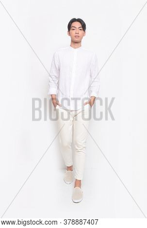 Full body Young handsome man with wearing casual t-shirt with white jeans pants standing hands in pockets runway, in studio