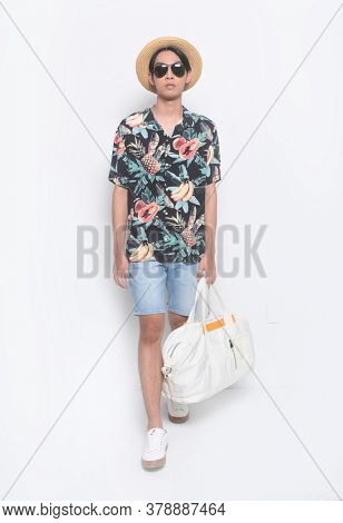 Full body Man casual wearing new stylish fruit printed T-shirts with blue pants shorts with hat, holding handbag runway in studio in studio