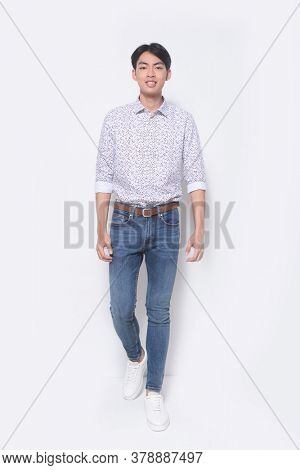Full body handsome man wearing plaid shirts and blue jeans posing with white sneakers runway, in studio