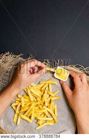 Fries-fried Potatoes With Sauce. Vertical Photo. A Mans Hands Eat Food. Flat Lay