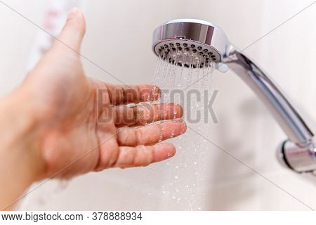Check The Temperature Of The Shower Water. A Mans Hand Under A Stream Of Water Selective Focus