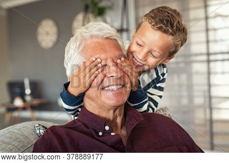 Happy little boy hiding his grandfather eyes with his hands. Happy grandson playing hide and seek with senior man at home. Playful child covering eyes of his grandfather, guess who game.