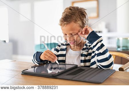 Creative kid drawing on tablet using digital pen. Child using pen on tablet to draw and complete homework. Cute little boy using stylus on screen and drawing pictures at home.