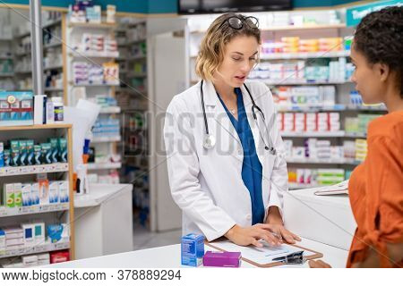 Woman pharmacist with prescription assisting a custome at the counter. Doctor in drugstore suggesting medical drug to buyer. Druggist with prescription explaining dosage of medicines to african woman.