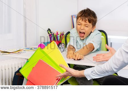 Boy With Autism Spectrum Disorder Throw Textbooks And Books From Table In Negative Expression Behavi