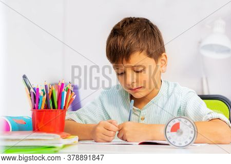 Little Boy Doing Writing Exercise With Lesson Timer