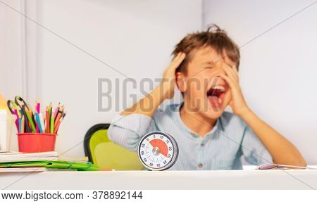 Sad Crying Autistic Boy Sitting During Development Therapy By The Desk With Lesson Timer Cover Face