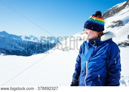 Portrait Of Girl In Winter Coat And Hat Walk High In The Mountain On Sunny Day