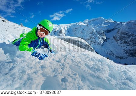 Cute Kid Skier Having Fun Laying In Snow Over Sunny Mountain Panorama Copy Space