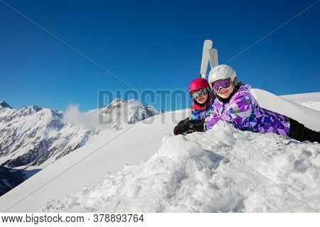 Two Girls Lay In The Snow Over Blue Sky And High Mountains With Ski On Background