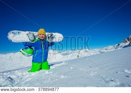 Portrait Of A Boy Holding Snowboard And Casual Hat Sit In Snow Over Mountain Panorama In Good Weathe