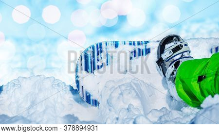 Close-up Of A Little Snowboard In Snow Attached To Child Legs With Lens Flares On Background