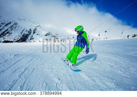 Motion Portrait Of A Boy On Snowboard Ride Downhill View From Behind On The Slope Track