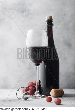 Homemade Red Wine In Bottle With Crystal Glass Corks With Vintage Corkscrew And Grapes On Light Tabl