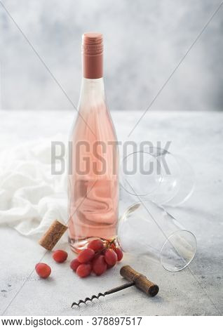 Bottle Of Pink Rose Wine With Grapes And Empty Glass With Corkscrew And Linen Cloth On Light Table B