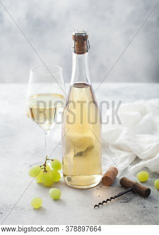 Bottle And Glass Of White Homemade Wine With Grapes And Corkscrew With Linen Cloth On Light Table Ba