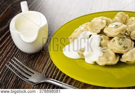 Sauce Boat With Sour Cream, Yellow Glass Plate With Meat Dumplings Poured Sour Cream, Fork On Dark W