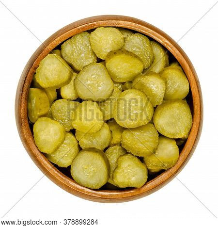 Pickled Cucumber Discs, Also Known As Pickle Or Gherkin, In Wooden Bowl. Small Pickled Cucumbers Wit