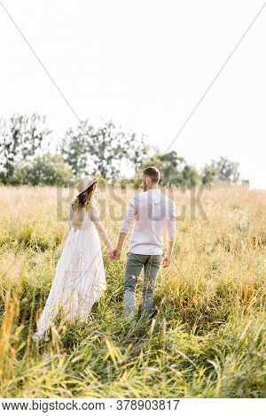A Happy Couple Enjoying Time In The Countryside. Man And His Pregnant Woman Smiling And Resting On T