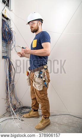 Electrician Builder At Work, Examines The Cable Connection In The Electrical Line In The Fuselage Of