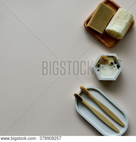 Soy Candle, Bamboo Toothbrushes On A Concrete Tray, Natural Soap And Loofah Sponge Bath On A Wooden