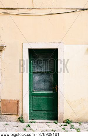 Green Doors With Shabby Dirty Windows Against The White Wall