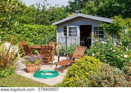 Shed With Flowered Terrace And Wooden Garden Furniture