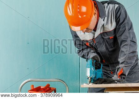 A Male Builder Cuts A Wooden Beam With An Electric Jigsaw, Male Hands With An Electric Jigsaw. Worki