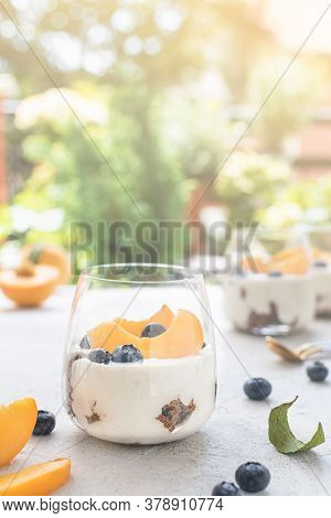 Individual Layered Desserts With Sponge Cake, Cream And Peach Fruit, Blueberry, Trifle
