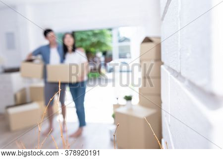 Blur Images Of Couple, Husband And  Wife Helping Each Other To Lift The Box Happily, To Move Into A
