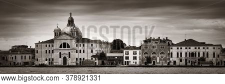 City skyline of Venice panorama with church and historical buildings viewed from waterfront in Italy.