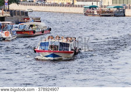 Russia, St.petersburg - July 22, 2020: Pleasure Boat With People Floats On The River In The City.