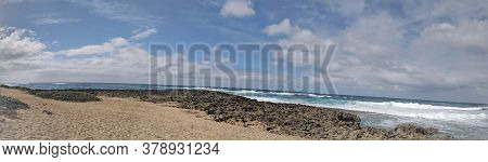 Panorama Of Waves Crash On Along Lava Rock Shore With Blue Sky At Turtle Bay Beach In The North Shor
