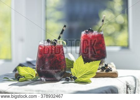 Two Glass Of Cold Ice Black Currant Juice With Ripe Berries And Green Leaves On Table In Sunny Room
