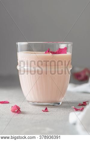 Glass Of Moon Milk With A Roses On On Light Concrete. Ayurvedic Relaxing Drink For The Night.