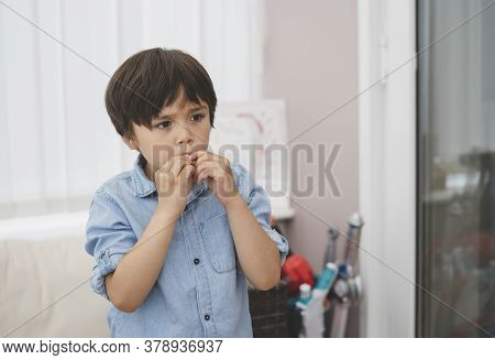 Portrait Of Kid Biting His Finger Nails While Looking At Something, Emotional Child Portrait Standin