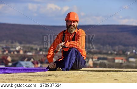 In Work Clothes. Roofer Working On Roof Structure Of Building On Construction Site. Roofer Wear Safe