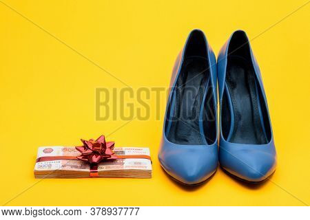Beautiful Womens Shoes And A Wad Of Money With A Gift Ribbon On A Yellow Background