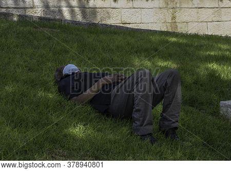 Jerusalem, Israel - July 30th, 2020: A man having a mid day power nap, wearing a COVID mask in a Jerusalem, Israel, park.