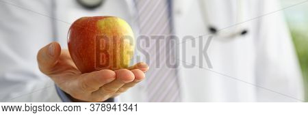 Male Medicine Therapeutist Doctor Hands Holding Red Fresh Ripe Apple. Medical Help Or Insurance Conc