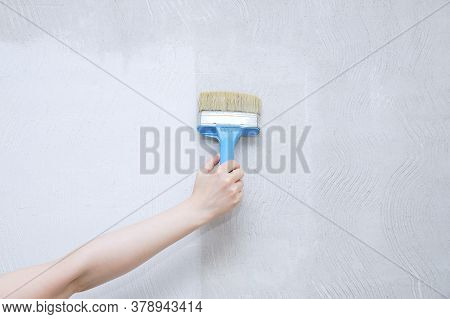 Home Improvement. Caucasian Woman Hand Priming A White Wall With A Brush.