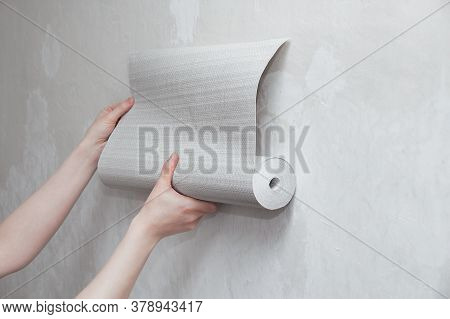 A Roll Of Gray Wallpaper In The Hands Of A Caucasian Woman. Attaches Wallpaper To The Wall.