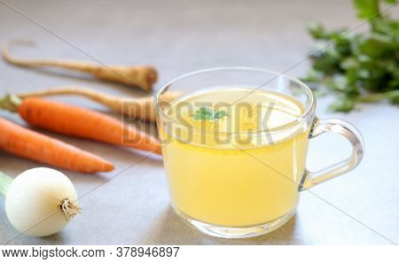 Clear Homemade Bone  Broth In The Glass Cup On The Table. Carrot,onion And Parsley Are Around. Horiz