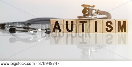 Autism The Word On Wooden Cubes, Cubes Stand On A Reflective White Surface, On Cubes - A Stethoscope