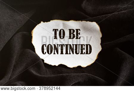 Burnt White Piece Of Paper With Text To Be Continued On A Black Fabric Background