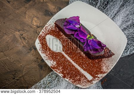 Chocolate Brownies  On Plate With Icing And Flowers