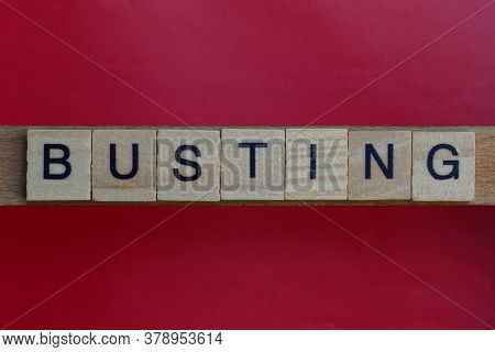 Text The Word Busting From Gray Wooden Small Letters With Black Font On An Red Table