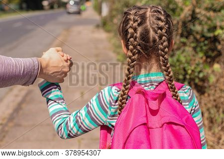 Back To School. Close-up A Dad, Father Or Parent Is Seeing Off Or Leading His Daughter With A Backpa
